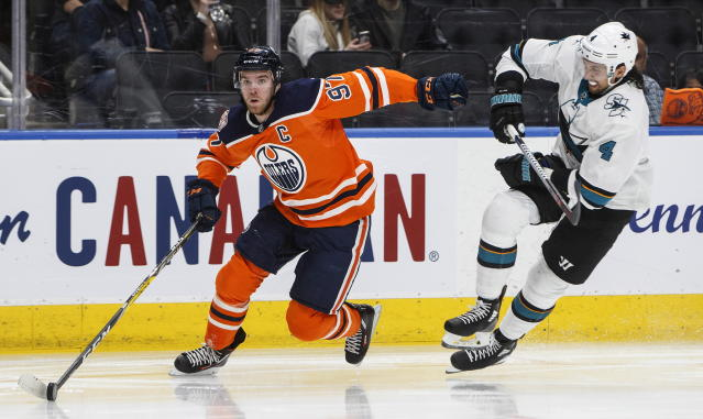 San Jose Sharks' Brenden Dillon (4) chases Edmonton Oilers' Connor McDavid (97) during the second period of an NHL hockey game Thursday, April 4, 2019, in Edmonton, Alberta. (Jason Franson/The Canadian Press via AP)