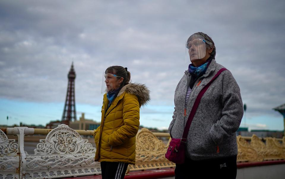 People wear face visors against Covid-19 as they walk on the Central Pier. The Lancashire region went into Tier 3 of Covid-19 lockdown restrictions at midnight last night - Christopher Furlong/Getty Images