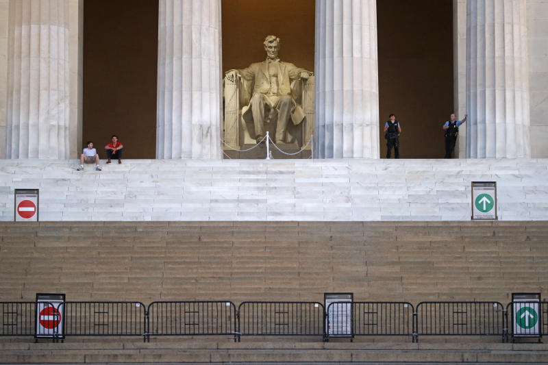 A sculpture of President Abraham Lincoln looks over visitors, left, and members of the U.S. Park Police, right, at the Lincoln Memorial as sunrise nears, Sunday, June 7, 2020, in Washington, the morning after massive protests over the death of George Floyd, who died after being restrained by Minneapolis police officers. (AP Photo/Patrick Semansky)