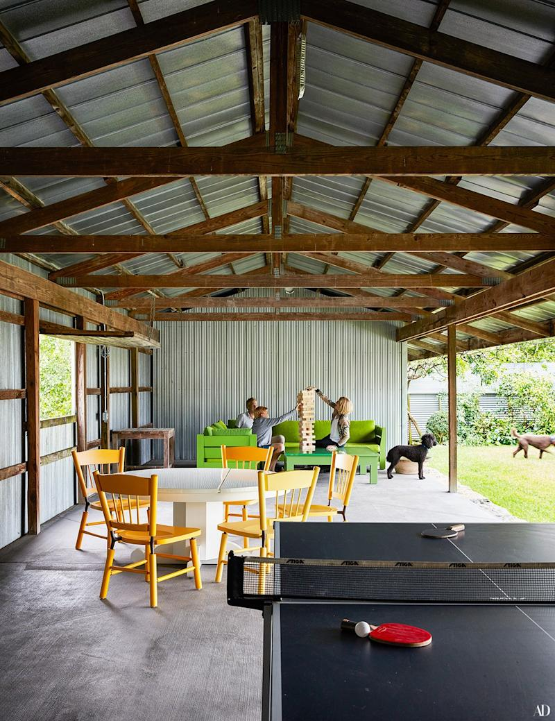 The family enjoys game time inside the corrugated-metal pool cabana designed by Roy McMakin.