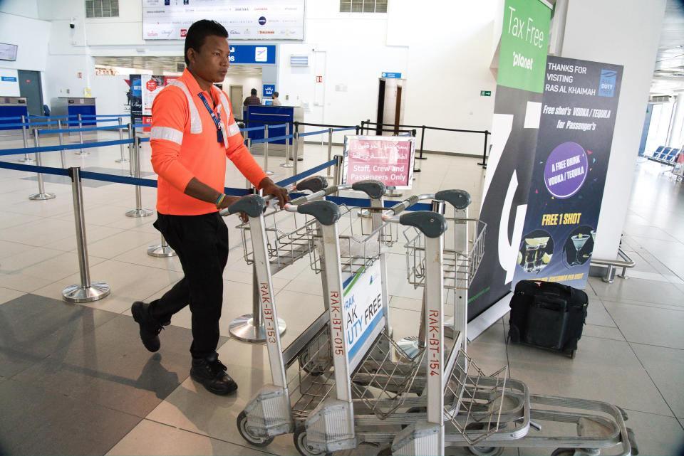 A worker pushes away luggage carts at the Ras al-Khaimah International Airport in Ras al-Khaimah, United Arab Emirates, Wednesday, Oct. 23, 2019. India's low-cost airline SpiceJet announced plans Wednesday to build its first international hub in the United Arab Emirates, offering a pledge of support to Boeing Co. by saying it would use now-grounded 737 MAX aircraft in the operation once regulators approve the planes for flight. (AP Photo/Jon Gambrell)