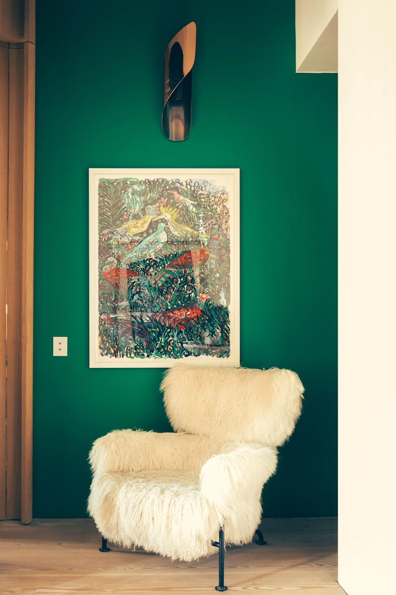 The green entrance in a Paris flat owned by designer François Champsaur is hung with a gouache by Portuguese artist Bela Silva. The armchair is Franco Albini for Cassina. The wall sconce was designed by Champsaur for Pouenat Ferronnier.