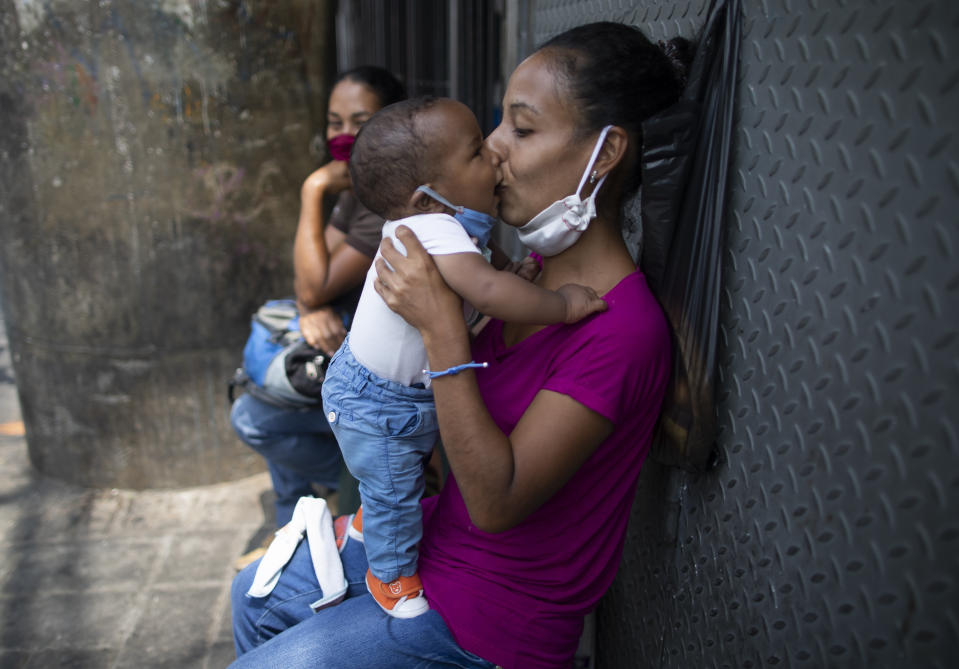 A mother kisses her baby, both equipped with protective face masks as a precaution against the spread of the new coronavirus, in Caracas, Venezuela, Thursday, May 21, 2020. (AP Photo/Ariana Cubillos)