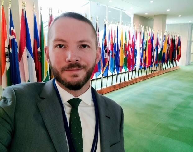 Newfoundland-born speechwriter Carl Mercer in front of member-state flags at the UN General Assembly. (Submitted by Carl Mercer - image credit)