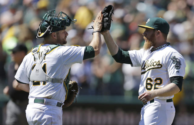 Oakland Athletics' Stephen Vogt, left, and pitcher Sean Doolittle celebrate the 4-2 defeat of the Texas Rangers at the end of a baseball game Wednesday, June 18, 2014, in Oakland, Calif. (AP Photo/Ben Margot)