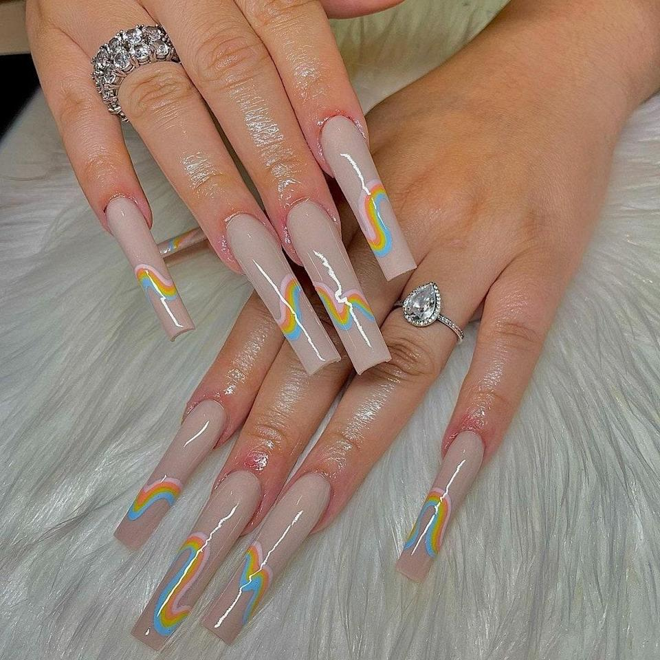 SlayByZay used a fabulous greige hue as the manicure base here. On top of the neutral-colored nail, she added squiggly lines of color that look like swirly rainbows on each nail. She also expertly sculpted each lengthy, square-shaped nail.