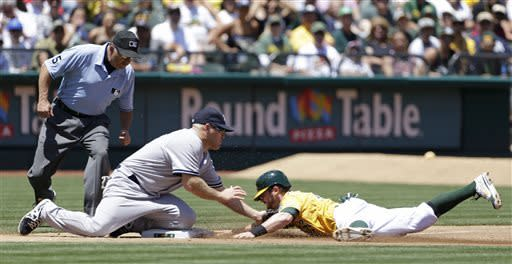 Oakland Athletics' Eric Sogard, right, is tagged out by New York Yankees third baseman Kevin Youkilis, center, on a steal-attempt during the third inning of a baseball game on Thursday, June 13, 2013, in Oakland, Calif. Third base umpire Dale Scott, left, looks on. (AP Photo/Eric Risberg)