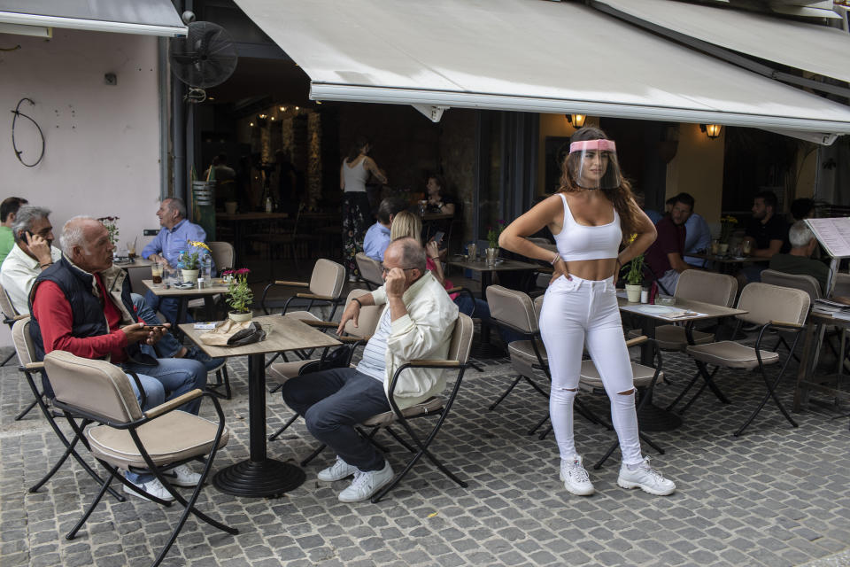 A cafe-restaurant staff stands outside a shop as people drink coffee in Monastiraki district of Athens, on Monday, May 25, 2020. Greece restarted regular ferry services to its islands Monday, and cafes and restaurants were also back open for business as the country accelerated efforts to salvage its tourism season. (AP Photo/Petros Giannakouris)