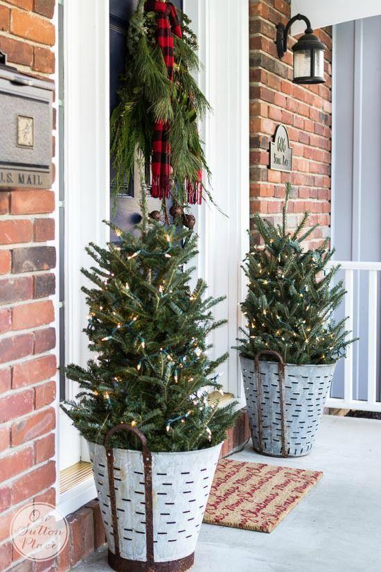 """<p>Who says Christmas trees should be reserved for December 25? Not us. Place mini trees in galvanized planters and stick them outside your front door for a beautiful outdoor display. </p><p><em><a href=""""https://www.onsuttonplace.com/festive-frugal-christmas-porch-decor/"""" rel=""""nofollow noopener"""" target=""""_blank"""" data-ylk=""""slk:See more at On Sutton Place »"""" class=""""link rapid-noclick-resp"""">See more at On Sutton Place »</a></em></p>"""