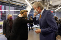 Actor Lin-Manuel Miranda, center, and New York Mayor Bill de Blasio, bump elbows before they tour the grand opening of a Broadway COVID-19 vaccination site intended to jump-start the city's entertainment industry, in New York, Monday, April 12, 2021. At left is Miranda's father, Luis A. Miranda, Jr. (AP Photo/Richard Drew, Pool)