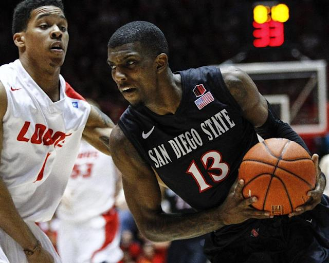San Diego State's Angelo Chol (13) drives to the basket against New Mexico's Cleveland Thomas (1) during the first half of an NCAA college basketball game at The Pit in Albuquerque, N.M., Saturday, Feb. 22, 2014. (AP Photo/Juan Antonio Labreche)