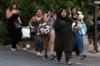 People cover their ears and carry their belongings as they flee their houses after heavy clashes in the coastal town of Khaldeh, south of Beirut, Lebanon, Sunday, Aug. 1, 2021. At least two people were killed on Sunday south of the Lebanese capital when gunmen opened fire at the funeral of a Hezbollah commander who was killed a day earlier, an official from the group said. (AP Photo/Bilal Hussein)