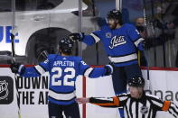 Winnipeg Jets' Adam Lowry (17) celebrates his goal against the Edmonton Oilers with teammate Mason Appleton (22) during the first period of an NHL hockey game, Sunday, Jan. 24, 2021 in Winnipeg, Manitoba. (Fred Greenslade/The Canadian Press via AP)