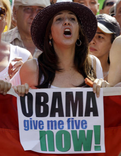 """FILE - In this May 12, 2012 file photo, Mariela Castro, daughter of Cuba's President Raul Castro, holds a sign demanding President Barack Obama release five Cuban intelligence agents imprisoned in U.S., popularly known as the """"Cuban Five,"""" before the start of a parade marking the upcoming International Day Against Homophobia, in Havana, Cuba. On the eve of her controversial arrival in the United States to attend a conference on Latin America Thursday, May 24, 2012, prominent academics say the 49-year-old Cuban first daughter has carved out an important name for herself that goes beyond her family lineage or famous last name, making gay rights her life's cause. (AP Photo/Javier Galeano, File)"""