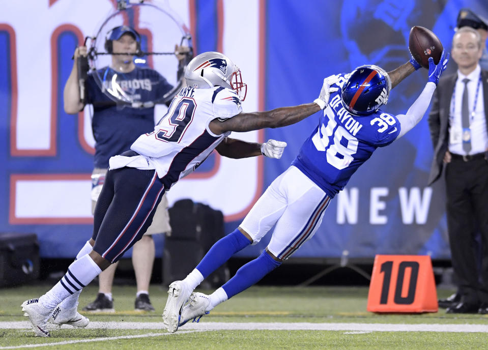 New York Giants cornerback Donte' Deayon (38) reaches to make an interception on a pass from New England Patriots quarterback Danny Etling, not pictured, intended for wide receiver K.J. Maye, left, during the first half of an NFL preseason football game, Thursday, Aug. 30, 2018, in East Rutherford. (AP Photo/Bill Kostroun)