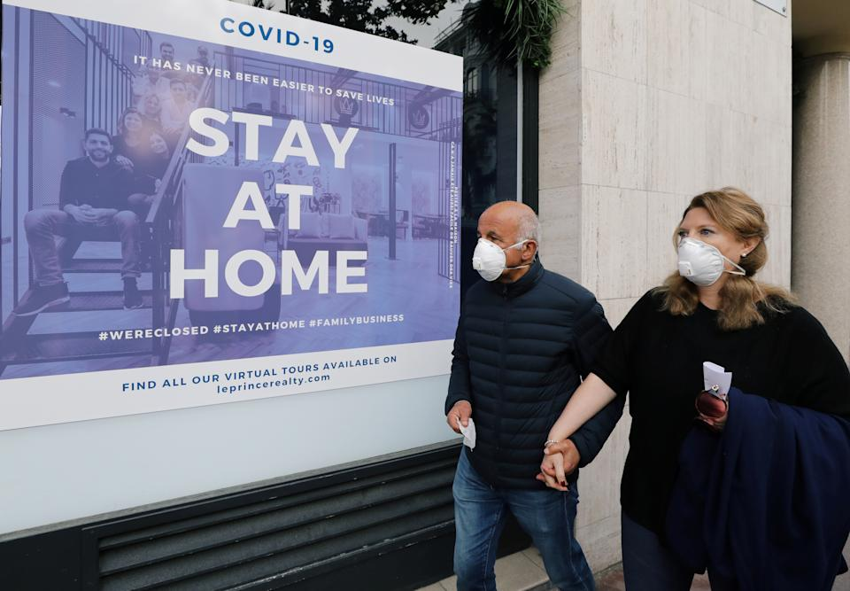 """People wearing protective face masks walk past a real estate agency where a sign reads """"Stay at home"""", as a lockdown is imposed to slow down the rate of the coronavirus disease (COVID-19) in Nice, France March 22, 2020.  REUTERS/Eric Gaillard"""