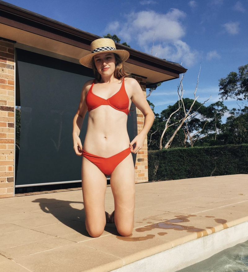 A photo of Maddison Brown wearing a red bikini and a straw hat next to a swimming pool.