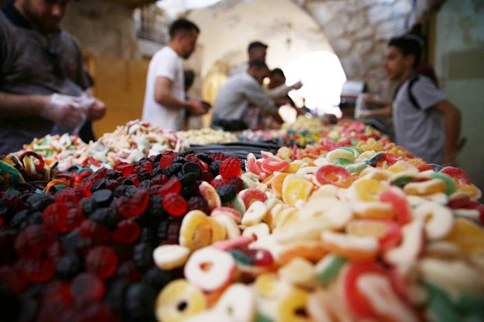 Sugared treats are seen close-up with buyers and vendors in the background.