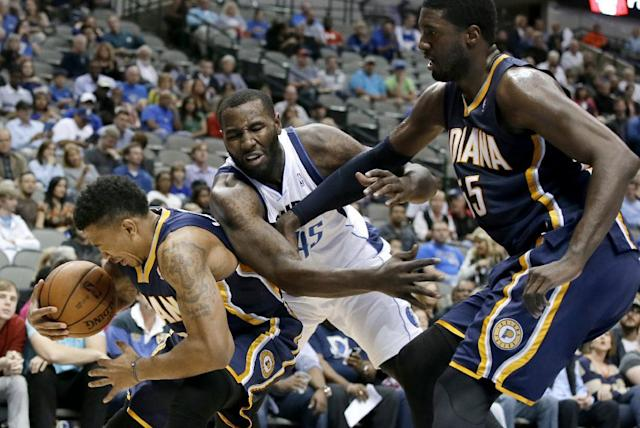 Indiana Pacers' Orlando Johnson, left, grabs a defensive rebound against Dallas Mavericks' DeJuan Blair, center, as the Pacers' Roy Hibbert, right, assists on the play in the first half of a preseason NBA basketball game Friday, Oct. 25, 2013, in Dallas. (AP Photo/Tony Gutierrez)