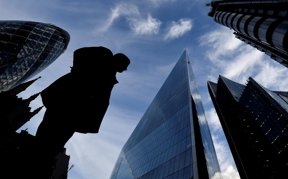 A man walks past The Gherkin and other office buildings in the City of London