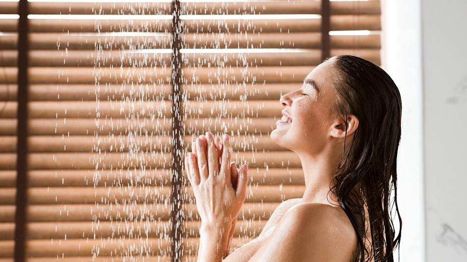 Woman Taking Shower Enjoying Water Splashing On Her, Side View