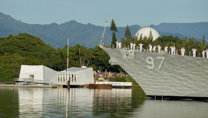 In this Dec. 7, 2016, file photo, sailors on the USS Halsey salute while passing by the USS Arizona Memorial during a moment of silence at Pearl Harbor, Hawaii. The bombing of that port sent the U.S. into World War II, a war that took more than 400,000 lives but galvanized the country.