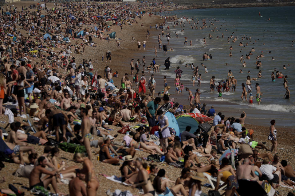 FILE - In this Wednesday, June 24, 2020 file photo on Britain's hottest day of the year so far with temperatures reaching 32.6 degrees Celsius (90 degrees Fahrenheit) at Heathrow airport, people relax on Brighton Beach in Brighton, England. More than 100,000 people have died in the United Kingdom after contracting the coronavirus. That's according to government figures released Tuesday Jan. 26, 2021. Britain is the fifth country in the world to pass that mark, after the United States, Brazil, India and Mexico, and by far the smallest. The U.S. has recorded more than 400,000 COVID-19 deaths, the world's highest total, but its population of about 330 million is about five times Britain's. (AP Photo/Matt Dunham, File)