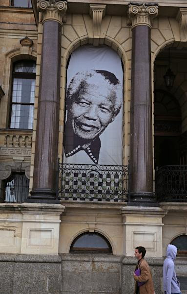 Pedestrian's walks beneath a giant portrait outside the City Hall in Cape Town, South Africa, Monday, June 24, 2013 at the spot where, on the balcony, former South Africa president Nelson Mandela, made his first public speech after being released from 27-years imprisonment. South African president Nelson Mandela remains in critical condition in a Pretoria hospital, President Jacob Zuma told journalists at a packed press briefing Monday, calling on people to pray for his recovery and the media not to demand details of his treatment or condition. (AP Photo/Schalk van Zuydam)