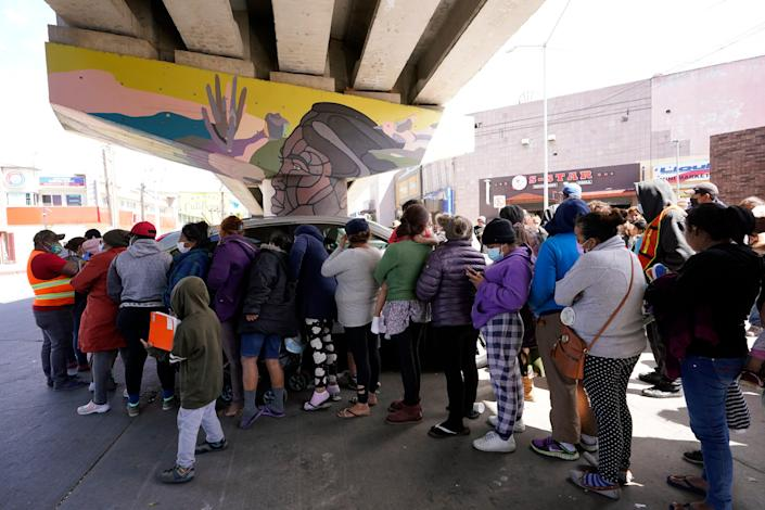 People surround a car as it arrives carrying food donations at a makeshift camp for migrants seeking asylum in the United States at the border crossing Friday, March 12, 2021, in Tijuana, Mexico. The Biden administration hopes to relieve the strain of thousands of unaccompanied children coming to the southern border by terminating a 2018 Trump-era order that discouraged potential family sponsors from coming forward to house the children.