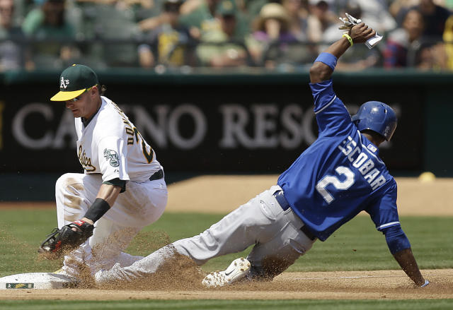 Kansas City Royals' Alcides Escobar, right, advances to third base past the tag of Oakland Athletics' Josh Donaldson in the fifth inning of a baseball game Sunday, Aug. 3, 2014, in Oakland, Calif. (AP Photo/Ben Margot)