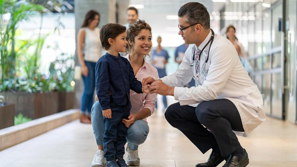 Male pediatrician talking to his little patient who is standing next to his mom all smiling - Incidental people at background.