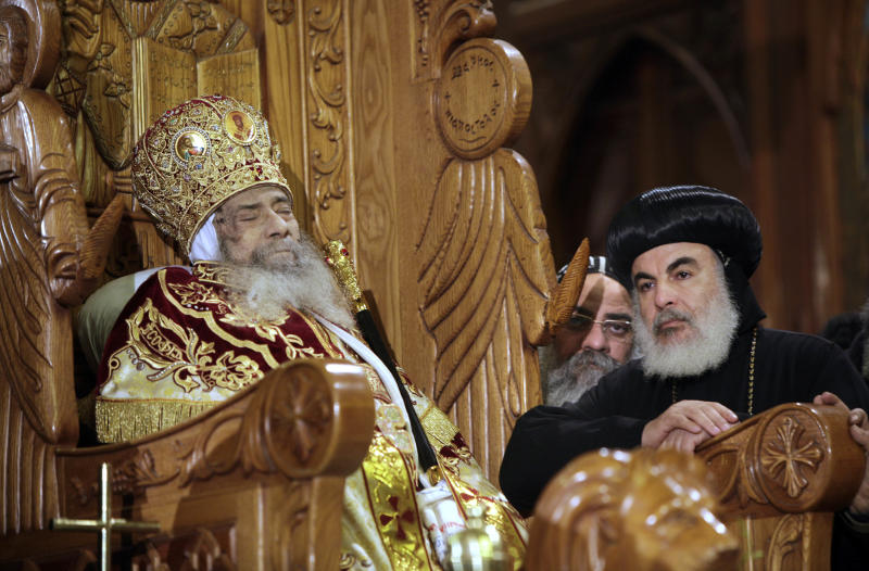 FILE -- In this Sunday, March 18, 2012 file photo, Archbishops stand next to the body of Pope Shenouda III seated on the throne of Mar Morqos, or St. Mark, as mourners gather for the viewing of the patriarch at the Coptic Orthodox cathedral in Cairo, Egypt, Sunday, March 18, 2012. Egypt's ancient Coptic Christian church named a new pope on Sunday, Nov. 4, 2012 to spiritually guide the community through a time when many fear for their future with the rise of Islamists to power and deterioration in police powers after last year's uprising. (AP Photo/Amr Nabil, file)