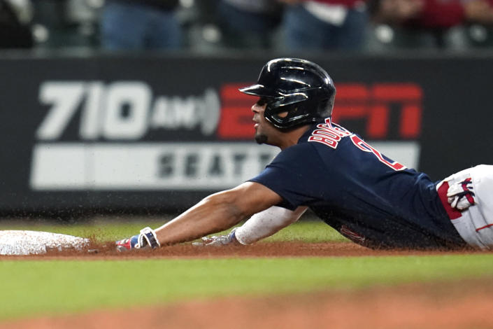Boston Red Sox's Xander Bogaerts slides into third base with a triple against the Seattle Mariners during the eighth inning of a baseball game Tuesday, Sept. 14, 2021, in Seattle. (AP Photo/Elaine Thompson)