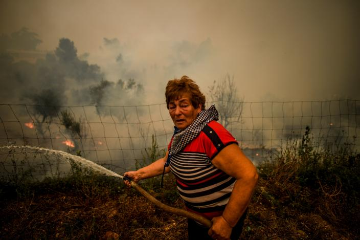 A villager uses a water hose to put out flames during a wildfire in Roda village in Macao, central Portugal on July 21, 2019. (Photo:Patricia De Melo Moreira/AFP/Getty Images)
