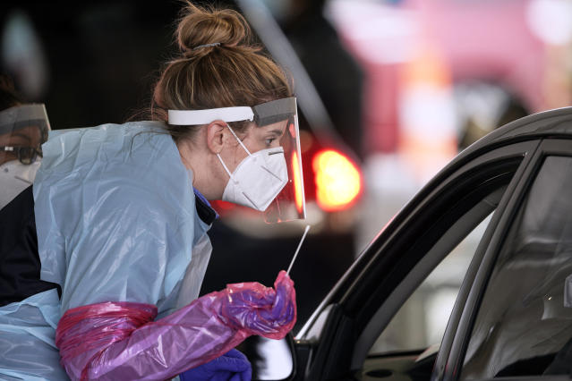 A nurse at a drive-through location in Omaha, Neb., on Monday holds a swab as she prepares to administer a test for the coronavirus. (Nati Harnik/AP)