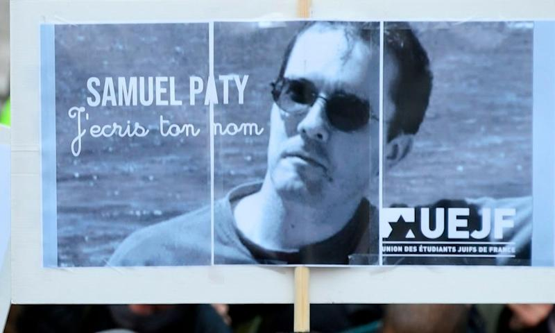 A placard with the portrait of history teacher Samuel Paty as people gather in Paris.