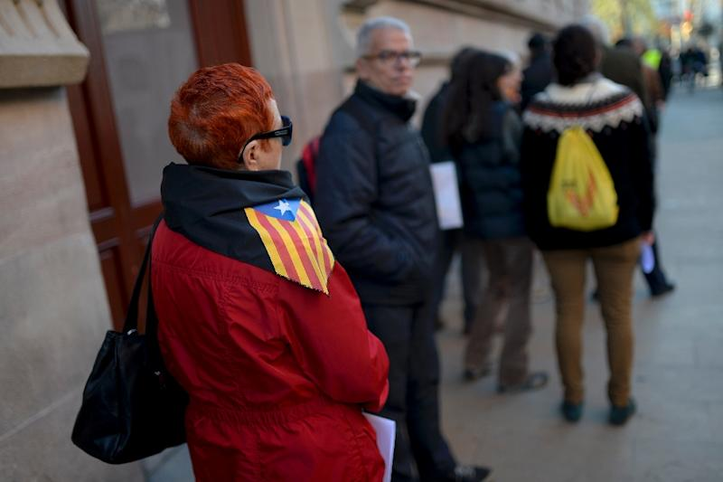 People queue outside the Superior Court of Justice of Catalonia building in Barcelona on December 23, 2014 in a movement to report themselves as participating in a November 9 non-binding vote on Catalan independence from Madrid