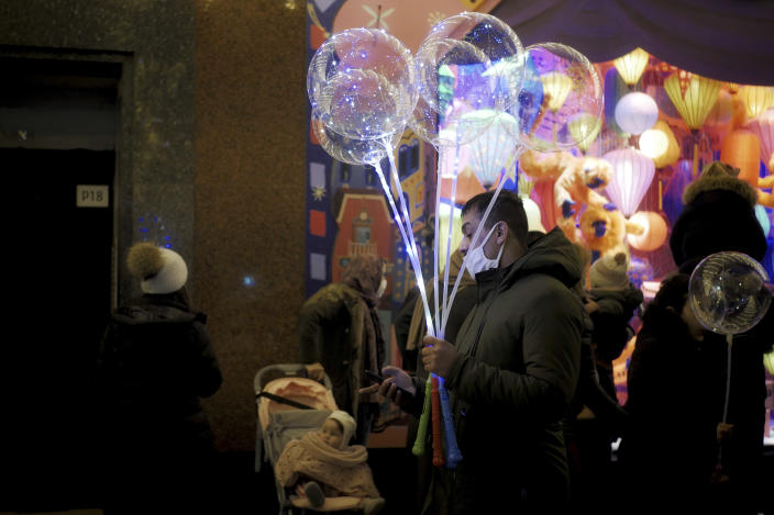 A man holds light balloons as he checks his phone on a sidewalk next to a department store in Paris, Thursday, Dec. 31, 2020. (AP Photo/Thibault Camus)