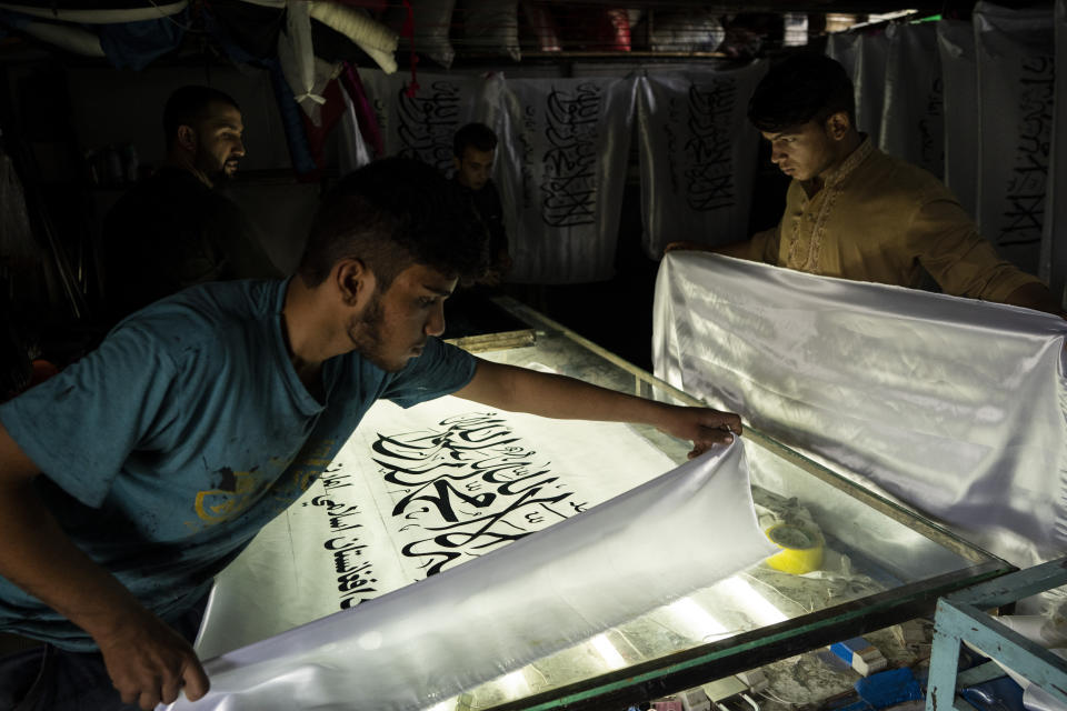 Workers hand-print Taliban flags in a small workshop in Kabul's Jawid market, Afghanistan, Sunday, Sept. 12, 2021. The flag shop, tucked away in the courtyard of a Kabul market, has documented Afghanistan's turbulent history over the decades with its ever-changing merchandise. Now the shop is filled with white Taliban flags, emblazoned with the Quran's Muslim statement of faith, in black Arabic lettering. (AP Photo/Bernat Armangue)