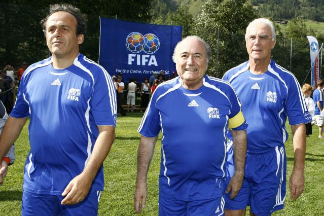 FILE - The Aug. 26, 2007 file photo shows FIFA President Sepp Blatter as he is framed by UEFA President and French football legend Michel Platini, left, and German soccer legend Franz Beckenbauer, right, as they arrive for a gala match between FIFA and Team 2000 in the 10th edition of the 'Sepp Blatter Tournament', in Ulrichen, Switzerland. Beckenbauer has been banned from football duty for 90 days for snubbing an investigation into Qatar's 2022 World Cup bid. FIFA said Friday, June 13, 2014 the 90-day provisional ban was requested by ethics prosecutor Michael Garcia. Beckenbauer was a voting member of FIFA's executive committee in December 2010 when it chose Qatar, and Russia as 2018 World Cup host. (AP Photo/Keystone, Laurent Gillieron)