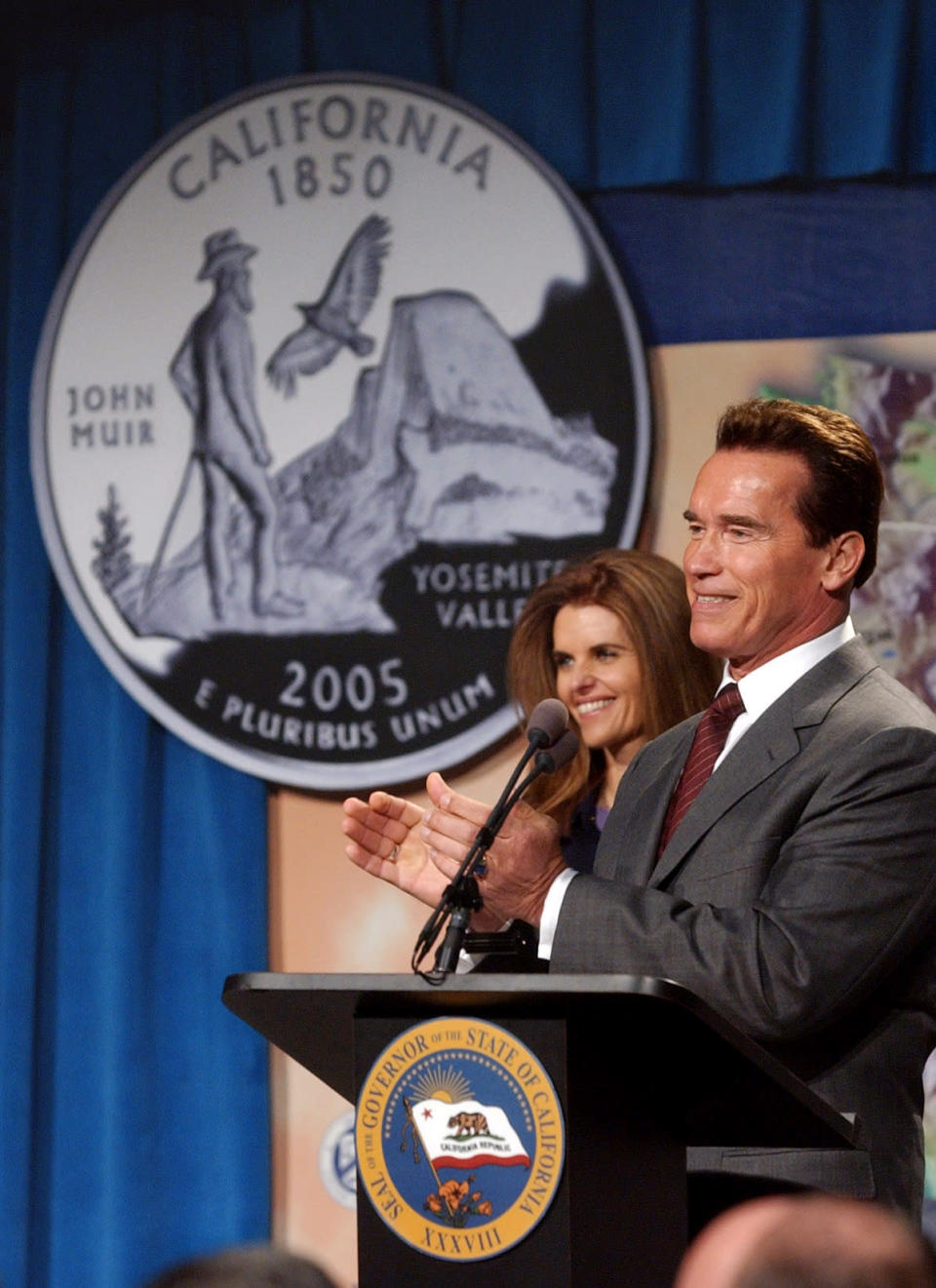 FILE - California Gov. Arnold Schwarzenegger and his wife Maria Shriver applaud during ceremonies to launch the John Muir commemorative quarter coin, reverse shown at left, in Sacramento, Calif., Monday, Jan. 31, 2005. The Sierra Club is reckoning with the racist views of founder John Muir, the naturalist who helped spawn environmentalism. The San Francisco-based environmental group said Wednesday that Muir was part of the group's history perpetuating white supremacy. Executive Director Michael Brune says Muir made racist remarks about Black people and Native Americans, though his views later evolved. (AP Photo/Rich Pedroncelli, File)