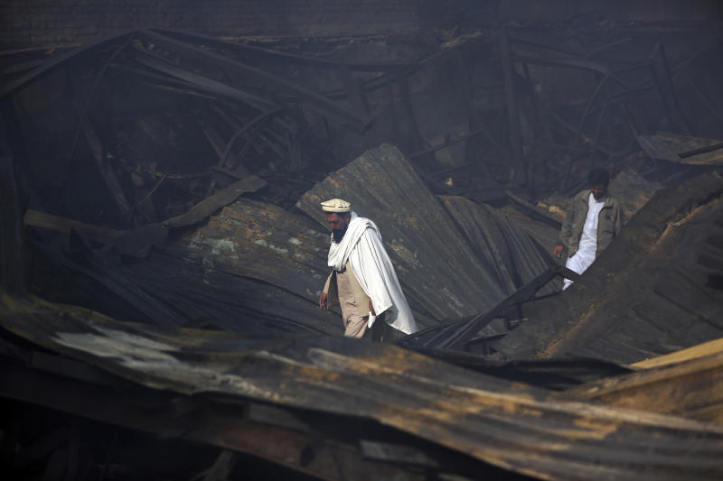 Men walk among the ruins after a fire devastated an electronic appliances market, in Kabul, Afghanistan, Friday, Nov. 2, 2018. Residents of the Afghan capital are grappling with the aftermath of a massive blaze that destroyed hundreds of stores at a market in Kabul.(AP Photo/Massoud Hossaini)