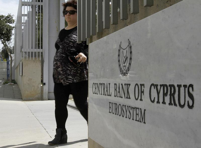 A woman exist from a gate of Cyprus central bank in Nicosia, Cyprus, Tuesday, March 13, 2012. International ratings agency Moody's downgraded euro member Cyprus into junk status Tuesday on heightened concerns over the exposure of its large banking sector to Greece. The agency reduced its rating on Cyprus by one notch to Ba1 and assigned a negative outlook, meaning that further downgrades are possible. (AP Photo/Petros Karadjias)