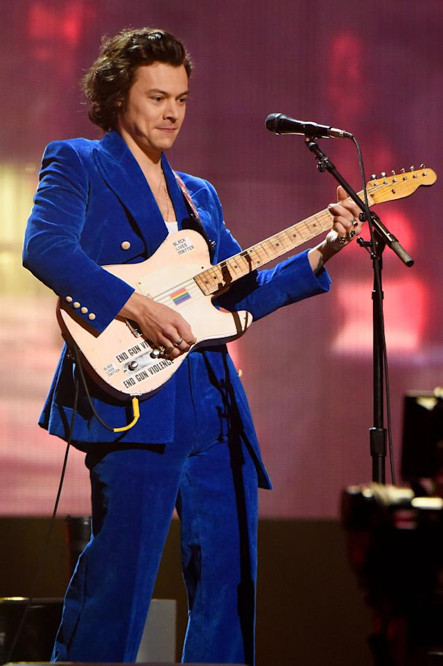 """<p>Harry started his fashion-forward year with a bang in this royal blue double-breasted Gucci suit to <a href=""""https://www.popsugar.com/entertainment/Stevie-Nicks-Harry-Styles-Rock-Hall-Performance-Video-2019-45976194"""" class=""""ga-track"""" data-ga-category=""""Related"""" data-ga-label=""""https://www.popsugar.com/entertainment/Stevie-Nicks-Harry-Styles-Rock-Hall-Performance-Video-2019-45976194"""" data-ga-action=""""In-Line Links"""">induct Stevie Nicks into the Rock and Roll Hall of Fame</a>. The velvet wide-leg suit is just one of many, many Gucci looks Harry's been rocking as of late.</p>"""