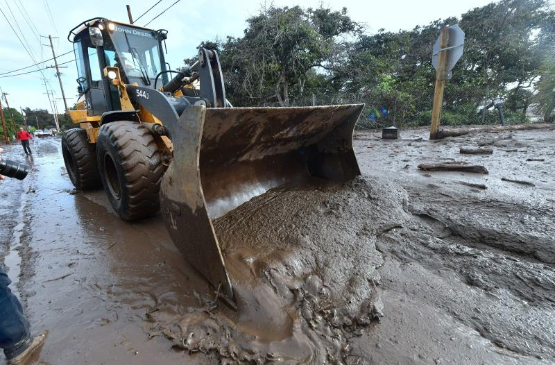 A bulldozer clears mud off the road near a flooded section of U.S. 101 near the San Ysidro exit in Montecito, California, on Tuesday. (FREDERIC J. BROWN via Getty Images)