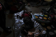 A man sleeps on a mattress inside a shelter for displaced Haitians, in Port-au-Prince, Haiti, Saturday, July 10, 2021, three days after Haitian President Jovenel Moise was assassinated in his home. The displaced Haitians were forced to flee their community where they had settled after the 2010 earthquake, after armed gangs set their homes on fire in late June. (AP Photo/Fernando Llano)