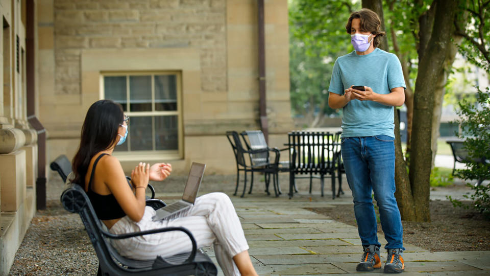 In this photo provided by Jason Koski and Cornell University, Bryan Maley, right, a grad student in the Master of Public Health program, interviews a student on campus about mask-wearing experiences as part of a public health survey, Friday, July 30, 2020, in Ithaca, N.Y. (Jason Koski/Cornell University via AP)