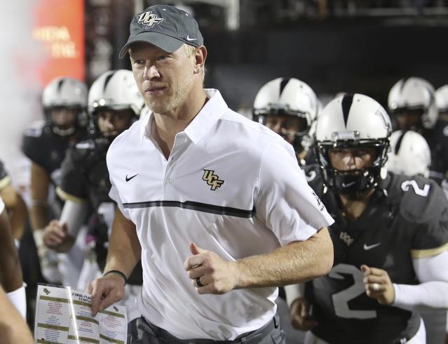 In this Oct. 15, 2016, file photo, Central Florida coach Scott Frost leads his team onto the field for an NCAA college football game against Temple in Orlando, Fla. (Stephen M. Dowell/Orlando Sentinel via AP, File)