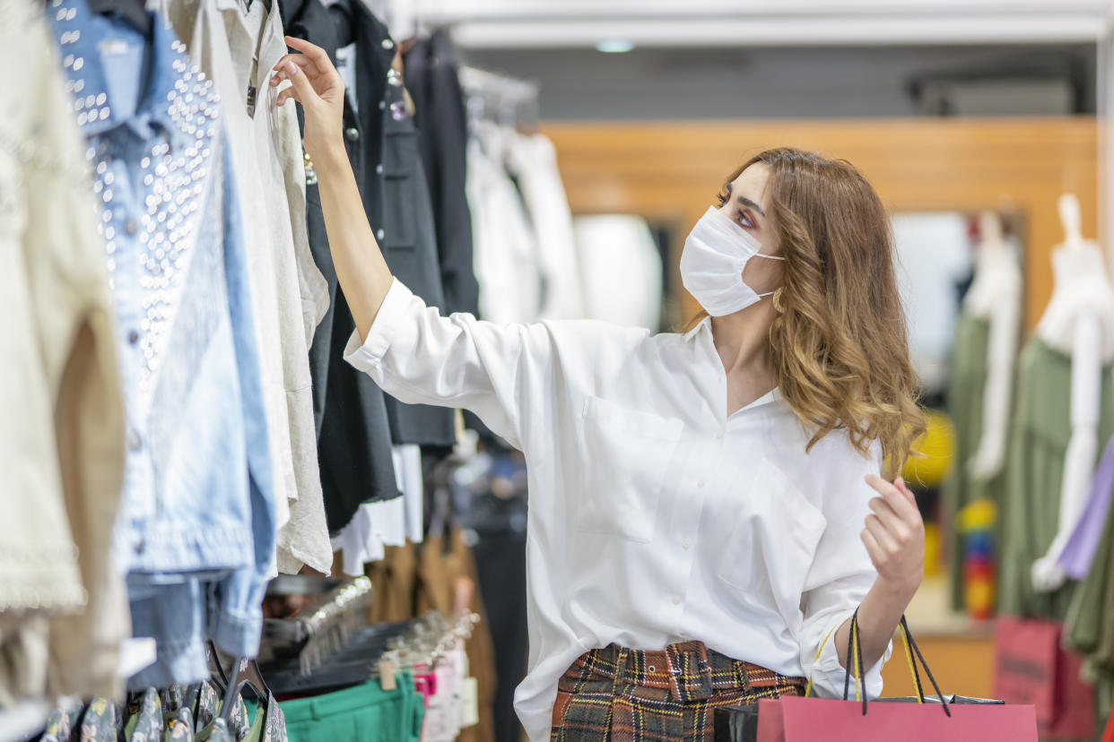 A young woman wears a protective mask while shopping.