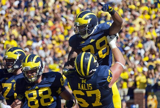 Michigan running back Fitzgerald Toussaint (28) celebrates his touchdown with offensive lineman Kyle Kalis (67) in the fourth quarter of an NCAA college football game against Akron in Ann Arbor, Mich., Saturday, Sept. 14, 2013. Michigan won 28-24. (AP Photo/Tony Ding)